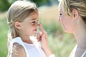 Mother and daughter putting sun protection on their face