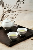 Tray of green tea with kettle against orchid painting on background