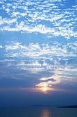 Sun setting in sky over ocean
