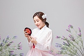 young woman wearing a hanbok and looking at a mirror