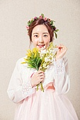 A beautiful Korean woman wearing a hanbok and holding a bouquet of flowers