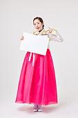 A beautiful Korean woman wearing a hanbok and holding a foam board