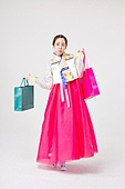 A Korean woman wearing a hanbok with a shopping bag