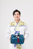 A Korean man in a hanbok holding a gift box