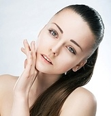 Beautiful young woman brunette face with a wellness complexion. Studio shot. Skincare beauty concept