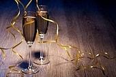 Pair glasses of champagne on the wooden background with the multi-coloured light