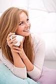 Young happy smiling woman holding white cup at home