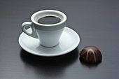 cup of coffee and chocolate candy on table