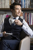 Young businessman drinking coffee in his study