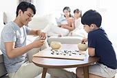 Little Chinese boy playing the game of Go with father