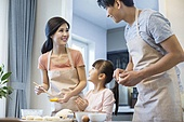 Happy young Chinese family baking together