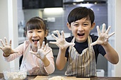 Happy Chinese siblings playing with flour