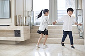 Happy Chinese siblings running in the living room