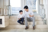 Cheerful Chinese father and son using electronic products in the living room