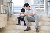 Cheerful Chinese father and son using digital tablet in the living room