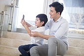 Cheerful Chinese father and son taking self portrait in the living room