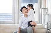 Cheerful Chinese daughter whispering to father in the living room