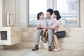 Cheerful Chinese family chatting in the living room