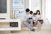 Cheerful young Chinese family reading a book in the living room