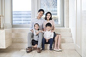 Portrait of cheerful young Chinese family in the living room