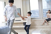 Cheerful Chinese father and son playing in the living room