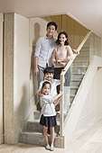 Portrait of cheerful young Chinese family on the stairs