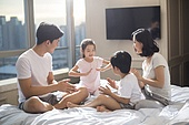 Cheerful young Chinese family having fun on a bed