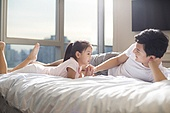 Cheerful young Chinese father playing with his daughter on bed
