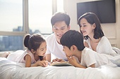 Cheerful young Chinese family reading a book on bed