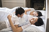 Cheerful Chinese boy waking up his parents in bedroom