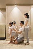 Cheerful young Chinese parents measuring their children's height