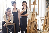 Young Chinese women painting in studio