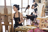 Young Chinese woman painting in art class
