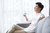 Cheerful young Chinese man drinking coffee at home