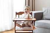 Cute Chinese baby boy sitting in high chair