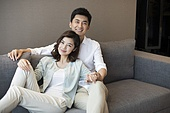 Cheerful young Chinese couple relaxing at home
