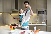 Chinese father holding baby and talking on the phone in kitchen