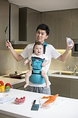 Chinese father holding baby and cooking in the kitchen