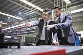 Businessman and engineer checking machine parts in the factory