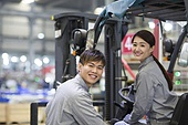 Confident Chinese workers driving forklift in the factory