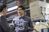 Chinese businessman and engineer talking in the factory