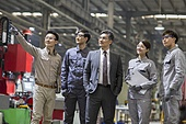 Confident Chinese businessman and engineering team in the factory