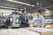 Businessman shaking hands with engineer in the factory