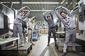 Chinese engineers stretching in the factory