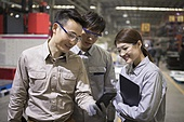 Confident Chinese engineers talking in the factory