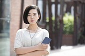 Beautiful young Chinese woman holding a smart phone