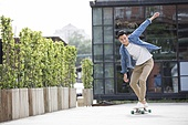 Cheerful young Chinese man skateboarding