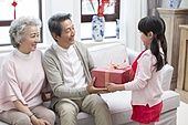 Granddaughter giving gift to grandparents during Chinese New Year