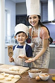 Happy young Chinese mother and son baking together