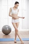 Young women measure waist circumference